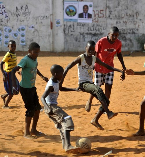 Children play soccer in front of a wall with election posters in the capital Maputo November 16, 2013. Mozambique goes to the polls for the municipal elections on November 22.  REUTERS/Grant Lee Neuenbur (MOZAMBIQUE  - Tags: POLITICS ELECTIONS)   - RTX15G7R